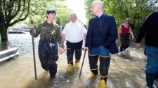 NDP Leader Jack Layton, right, takes a walk along a street immersed in flood waters alongside St-Paul fire chief Gilles Bastien, centre, and Major Marieeve Begin in the town of St-Paul-de-I'lle-aux-Noix, Que., Monday, May 30, 2011. (Graham Hughes / THE CANADIAN PRESS)