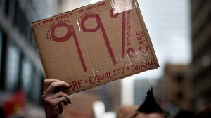 A sign held by a protester marching near Toronto's financial district on Oct. 15, 2011. A new poll finds Canadians agree there is a growing income gap, but not on who or what to blame.
